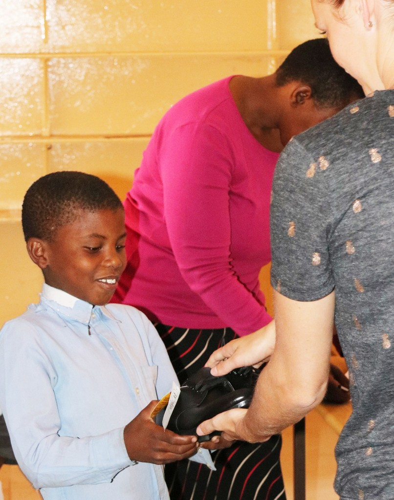 A-Mabele-Primary-School-student-receives-his-new-shoes-from-Ngoma-Safari-Lodge-manager-Frances-van-Pletzen