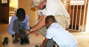 Mabele-Primary-School-students-try-on-their-new-shoes-with-Ngoma-Safari-Lodge-manager-Jarryd-King